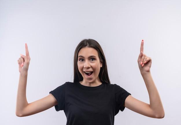 Радостная молодая кавказская девушка в черной футболке указывает на изолированную белую стену