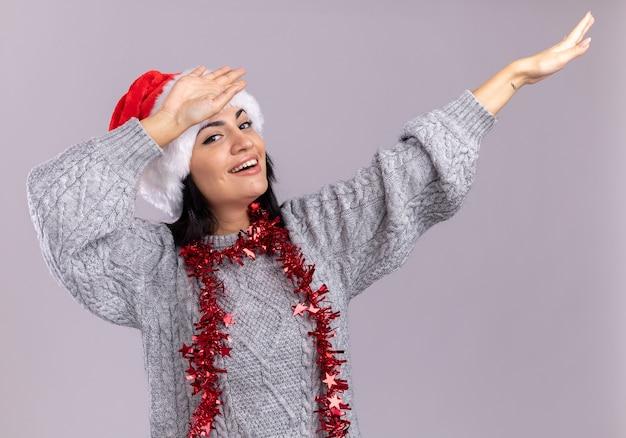 クリスマスの帽子と白い壁に分離された軽くたたくジェスチャーをしている首の周りに見掛け倒しの花輪を身に着けているうれしそうな若い白人の女の子