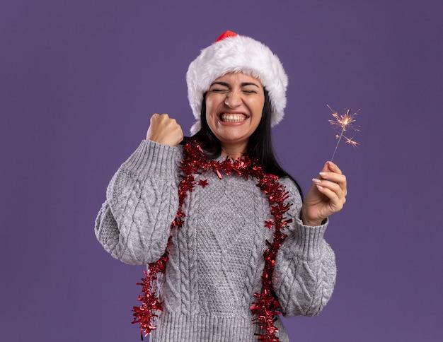 クリスマスの帽子と首の周りに見掛け倒しの花輪を身に着けているうれしそうな若い白人の女の子は、紫色の背景に分離された目を閉じてイエスのジェスチャーをしている休日の線香花火を保持しています