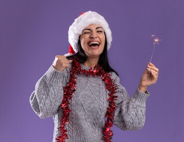 Радостная молодая кавказская девушка в рождественской шапке и гирлянде из мишуры на шее держит праздничный бенгальский огонь, делая жест да с закрытыми глазами, изолированными на фиолетовом фоне