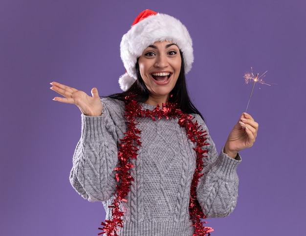 Радостная молодая кавказская девушка в рождественской шапке и гирлянде из мишуры на шее держит праздничный бенгальский огонь, глядя в камеру, показывая пустую руку, изолированную на фиолетовом фоне