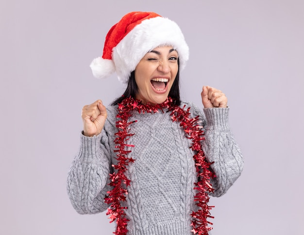 Радостная молодая кавказская девушка в рождественской шапке и гирлянде из мишуры на шее, глядя в камеру, подмигивая, делая жест `` да '' на белом фоне
