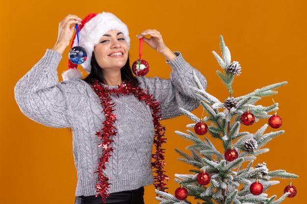 オレンジ色の壁に分離された頭の近くにクリスマスのつまらないものを保持している飾られたクリスマス ツリーの近くに立って、クリスマスの帽子と見掛け倒しの花輪を身に着けているうれしそうな若い白人の女の子