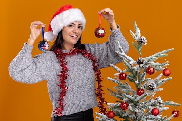 Радостная молодая кавказская девушка в новогодней шапке и мишурной гирлянде на шее стоит возле украшенной елки с рождественскими шарами возле головы, изолированной на оранжевой стене