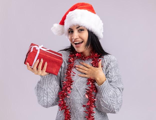 Gioiosa giovane ragazza caucasica che indossa il cappello di natale e la ghirlanda di orpelli intorno al collo che tiene il pacchetto regalo che fa gesto di ringraziamento isolato sulla parete bianca