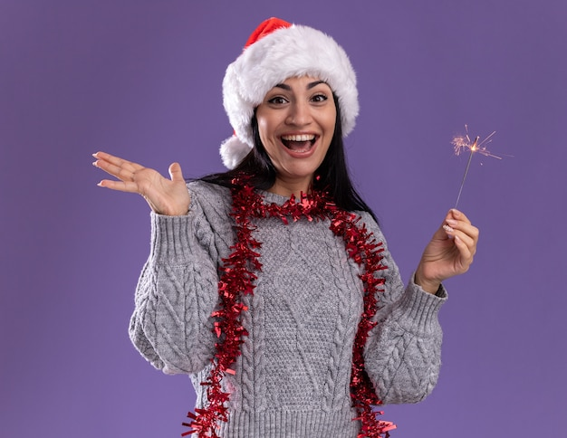 Gioiosa giovane ragazza caucasica che indossa il cappello di natale e la ghirlanda di orpelli intorno al collo che tiene lo sparkler di vacanza che guarda l'obbiettivo che mostra la mano vuota isolata su fondo viola