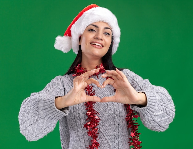 Joyful young caucasian girl wearing christmas hat and tinsel garland around neck looking at camera doing heart sign isolated on green background