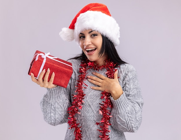 Gioiosa giovane ragazza caucasica che indossa il cappello di natale e la ghirlanda di orpelli intorno al collo che guarda l'obbiettivo che tiene il pacchetto regalo facendo gesto di ringraziamento isolato su priorità bassa bianca