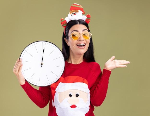 Радостная молодая кавказская девушка в головной повязке санта-клауса и свитере с очками держит часы, показывая пустую руку, изолированную на оливково-зеленой стене