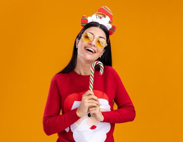 オレンジ色の背景に分離されたカメラを垂直に見ている伝統的なクリスマスのキャンディケインを保持しているメガネとサンタクロースのヘッドバンドとセーターを着てうれしそうな若い白人の女の子