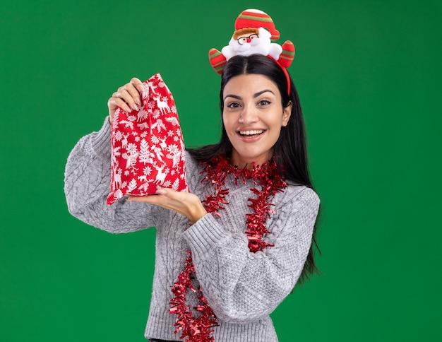 Радостная молодая кавказская девушка в головной повязке санта-клауса и гирлянде из мишуры на шее держит рождественский подарочный мешок, глядя в камеру, изолированную на зеленом фоне