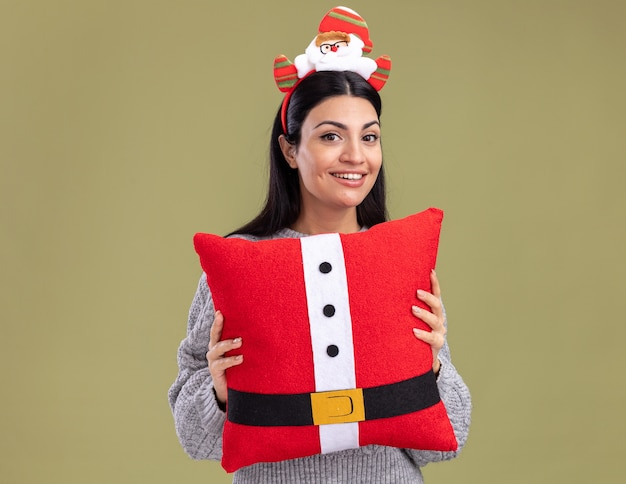 Joyful young caucasian girl wearing santa claus headband holding santa claus pillow looking at camera isolated on olive green background