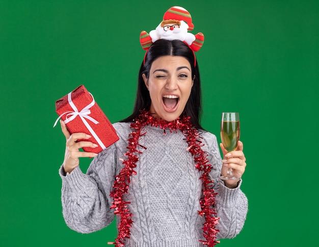 Gioiosa giovane ragazza caucasica che indossa la fascia di babbo natale e la ghirlanda di orpelli intorno al collo che tiene il pacchetto regalo e un bicchiere di champagne che guarda l'obbiettivo ammiccante isolato su priorità bassa verde