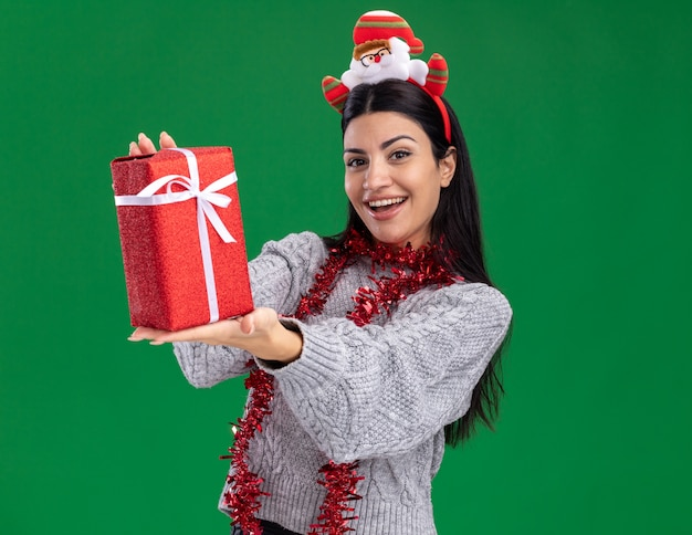 Joyful young caucasian girl wearing santa claus headband and tinsel garland around neck stretching out gift package towards camera looking at camera isolated on green background