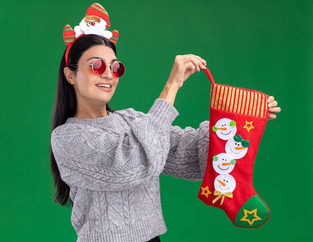 緑の背景に分離されたカメラを見てクリスマスの靴下を保持しているメガネとサンタクロースのヘッドバンドを身に着けているうれしそうな若い白人の女の子