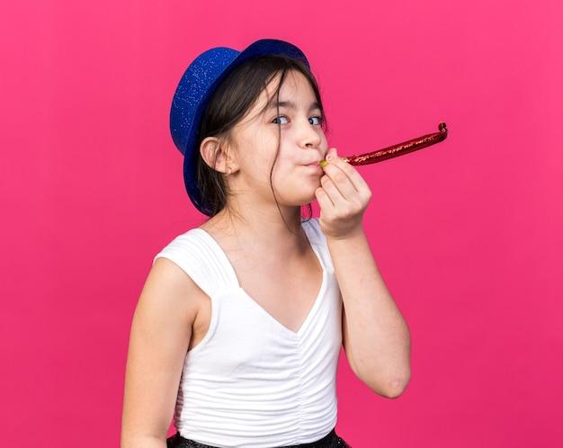 Радостная молодая кавказская девушка в синей партийной шляпе дует свисток на розовой стене с копией пространства