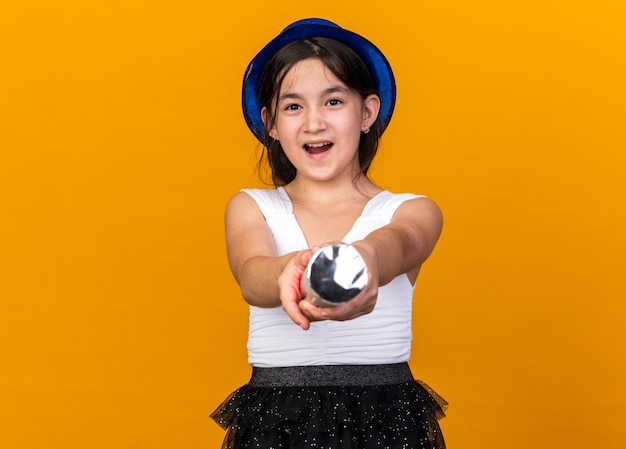 Joyful young caucasian girl with blue party hat holding confetti cannon isolated on orange wall with copy space