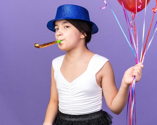 Радостная молодая кавказская девушка в синей партийной шляпе держит гелиевые шары и дует партийный свисток, изолированную на фиолетовой стене с копией пространства