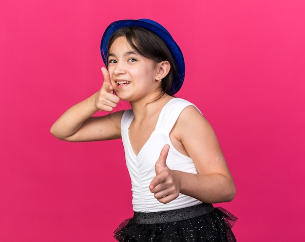 Joyful young caucasian girl with blue party hat pointing  isolated on pink wall with copy space