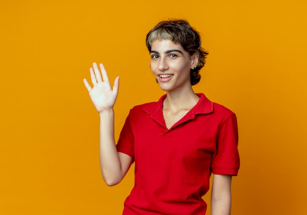 Joyful young caucasian girl with pixie haircut doing hi gesture at camera isolated on orange background with copy space