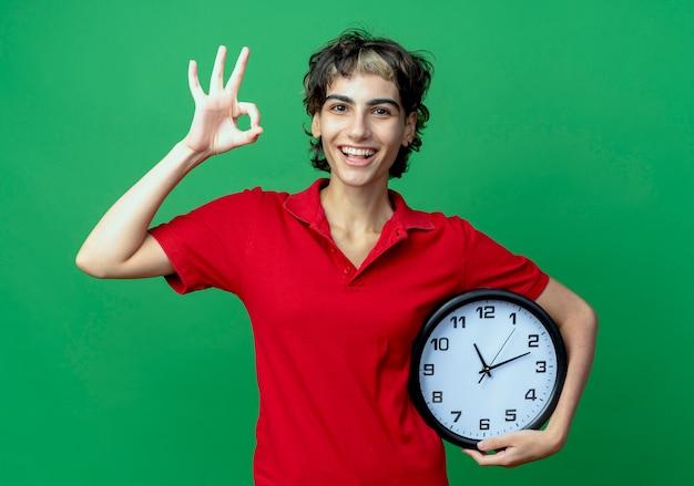 Радостная молодая кавказская девушка с прической пикси держит часы и делает знак ок, изолированные на зеленом фоне