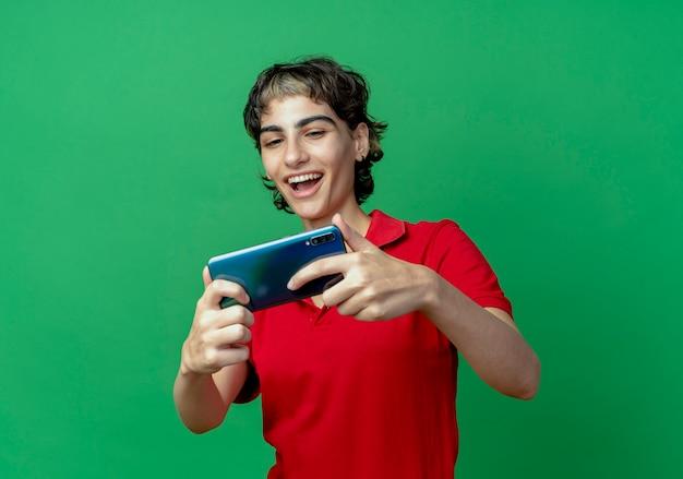 Gioiosa giovane ragazza caucasica con pixie haircut holding e guardando il telefono cellulare isolato su sfondo verde con copia spazio