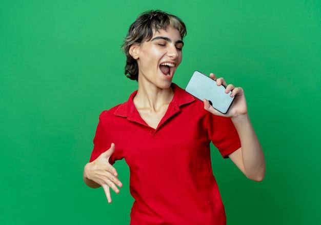 Радостная молодая кавказская девушка с прической пикси, держащая мобильный телефон, притворяется, что поет, используя телефон в качестве микрофона, держа руку в воздухе с закрытыми глазами, изолированными на зеленом фоне с копией пространства