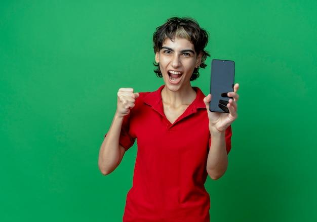 Радостная молодая кавказская девушка со стрижкой пикси показывает мобильный телефон и сжимает кулак, изолированную на зеленом фоне с копией пространства