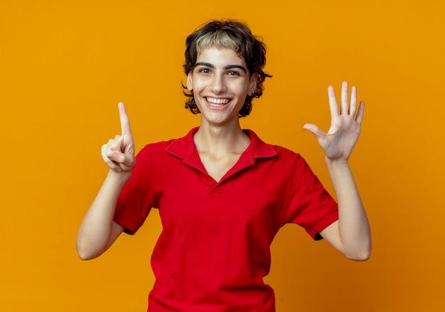 오렌지 배경에 고립 된 손으로 6을 보여주는 픽시 머리와 즐거운 젊은 백인 여자