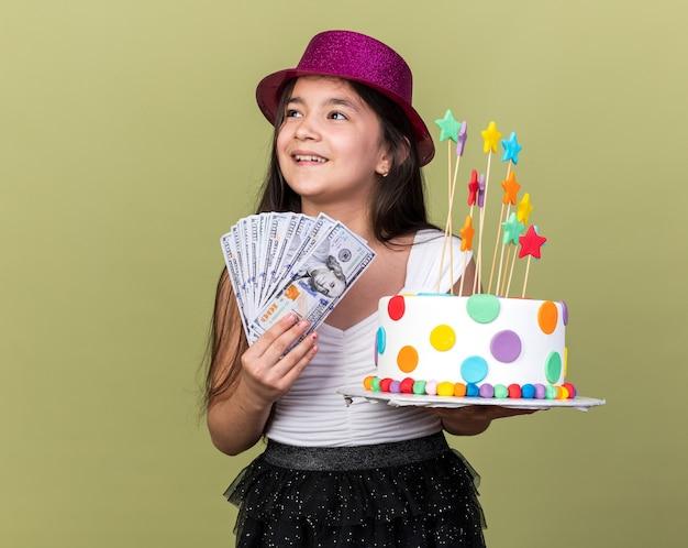 コピースペースのあるオリーブグリーンの壁に隔離された側を見て誕生日ケーキとお金を保持している紫色のパーティーハットと楽しい若い白人の女の子