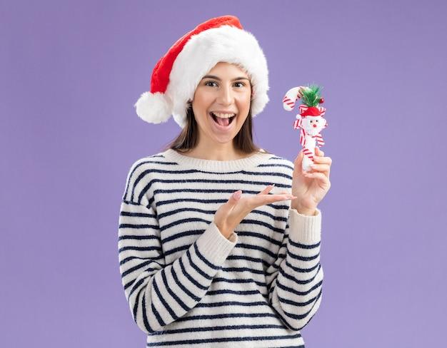Gioiosa giovane ragazza caucasica con cappello da babbo natale che tiene e indica un bastoncino di zucchero isolato su una parete viola con spazio per le copie