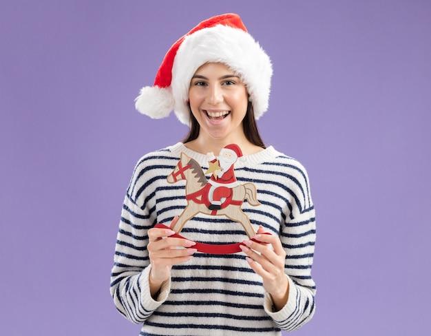 Joyful young caucasian girl with santa hat holding santa on rocking horse decoration
