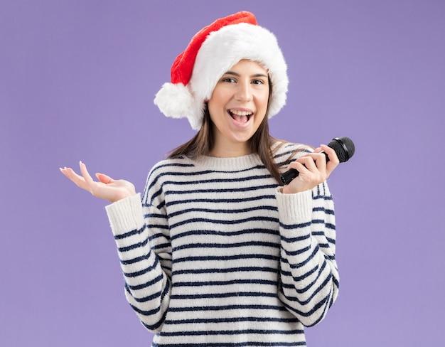 Радостная молодая кавказская девушка в шляпе санта-клауса держит микрофон и держит руку открытой