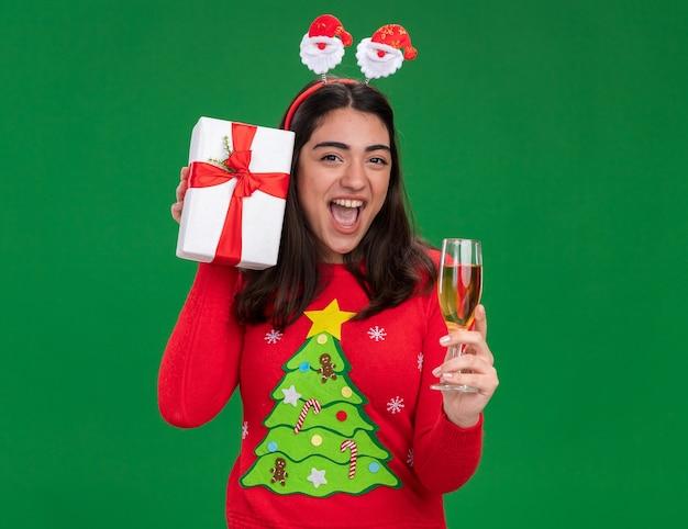 산타 머리띠와 함께 즐거운 젊은 백인 여자는 샴페인과 크리스마스 선물 상자의 유리를 보유하고 복사 공간이 녹색 배경에 고립