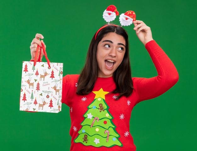 サンタのヘッドバンドを持つうれしそうな若い白人の女の子は、コピースペースで緑の背景に分離された側を見て紙のギフトバッグを保持します。