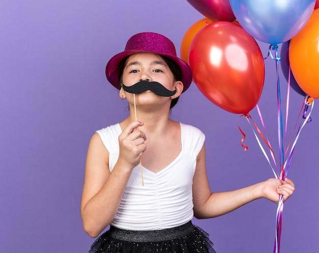 コピースペースと紫色の壁に分離された棒にヘリウム気球と偽の口ひげを保持している紫色のパーティハットを持つ楽しい若い白人の女の子
