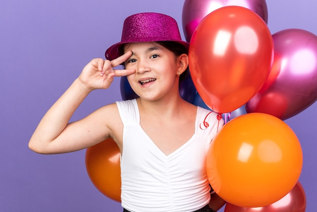 Joyful young caucasian girl with violet party hat holding helium balloons and gesturing victory sign isolated on purple wall with copy space