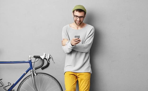 수염과 즐거운 젊은 백인 소식통 세련 된 비디오 게임 onweb 사용 전자 가제트를 입고. 휴대 전화에 와이파이를 사용하여 인터넷 서핑 안경에 행복 웃는 남자 사이클