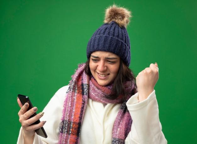 Gioiosa giovane ragazza malata caucasica che indossa abito invernale cappello e sciarpa tenendo e guardando il telefono cellulare facendo sì gesto con il tovagliolo in mano isolato sulla parete verde