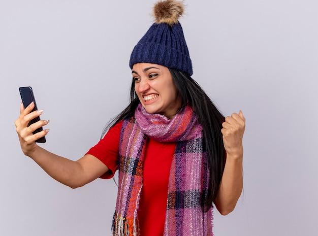Gioiosa giovane ragazza malata caucasica che indossa cappello invernale e sciarpa che tiene e guardando il telefono cellulare facendo sì gesto isolato sulla parete bianca con lo spazio della copia