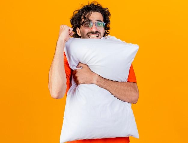 コピースペースでオレンジ色の背景に分離されたカメラを見てはいジェスチャーをしている枕を保持している眼鏡をかけているうれしそうな若い白人の病気の男