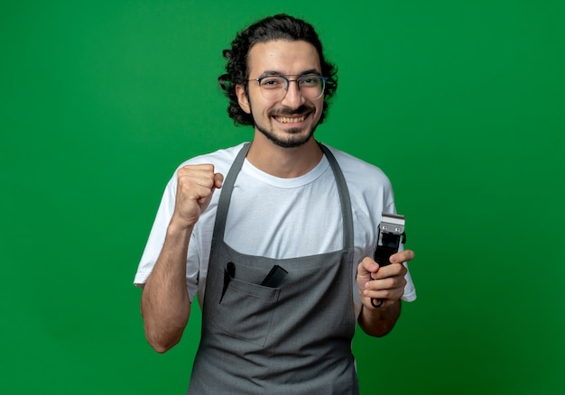 Joyful young caucasian male barber wearing glasses and wavy hair band in uniform holding hair clippers and clenching fist isolated on green background with copy space