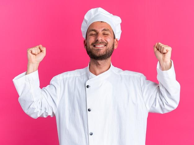 Gioioso giovane maschio caucasico cuoco in uniforme da chef e berretto che fa un gesto di sì con gli occhi chiusi isolati su una parete rosa
