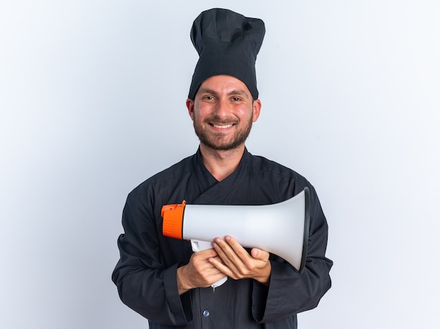 Joyful young caucasian male cook in chef uniform and cap holding speaker looking at camera isolated on white wall