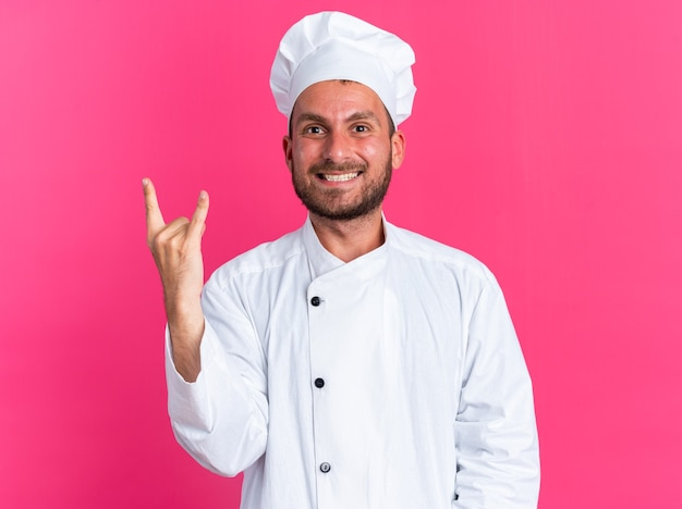 Joyful young caucasian male cook in chef uniform and cap looking at camera doing rock sign isolated on pink wall