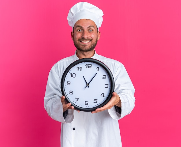 Joyful young caucasian male cook in chef uniform and cap looking at camera stretching out clock towards camera isolated on pink wall