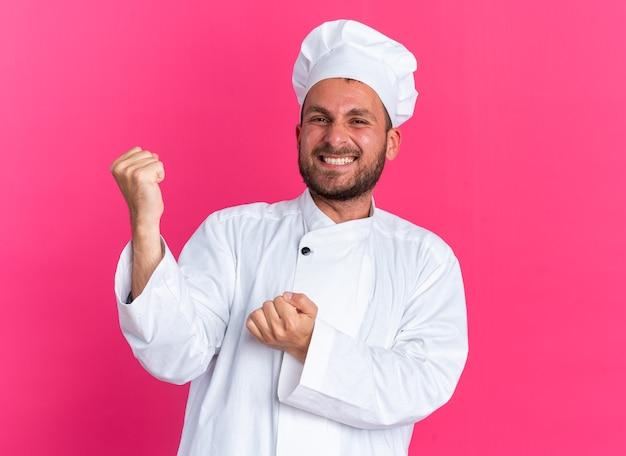 Радостный молодой кавказский повар в униформе шеф-повара и кепке делает жест `` да ''