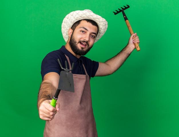 コピースペースと緑の壁に分離された熊手とくわ熊手を保持している園芸帽子を身に着けている楽しい若い白人男性の庭師