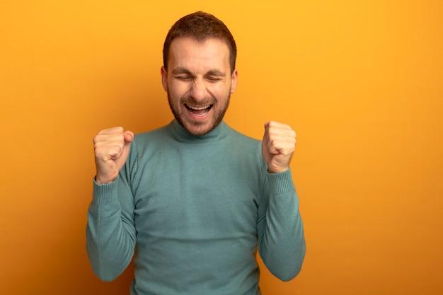 Gioioso giovane uomo caucasico che fa il gesto di sì con gli occhi chiusi isolato sulla parete arancione con lo spazio della copia