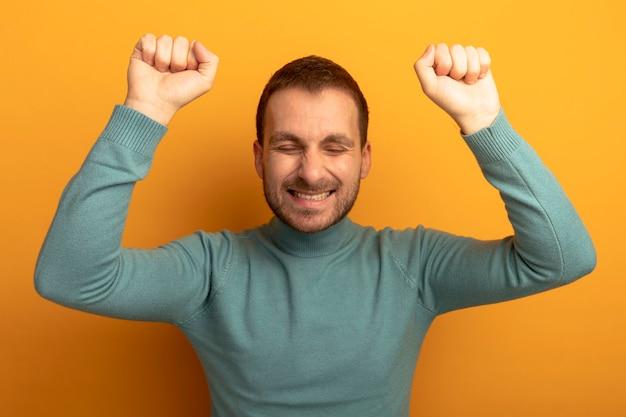 Gioioso giovane uomo caucasico facendo sì gesto con gli occhi chiusi isolati sulla parete arancione